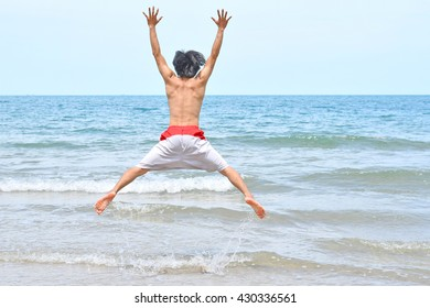 A man jumps in ocean waves. Jump with splashing water Summer Sunny Day