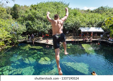 Man jumps off a cliff into a cenote in Mexico