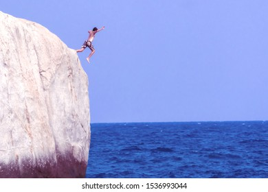 A man jumps off a cliff into the sea