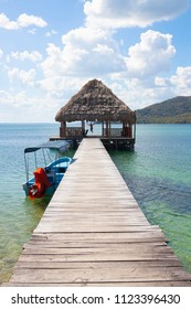 Man jumps off a wooden pier nto crystal clear blue lake in Guatemala, North America