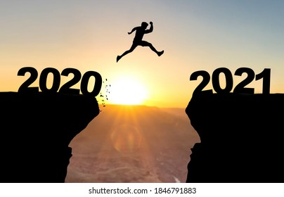 Man jumps over abyss in front of sunset with the inscription 2020 and 2021.