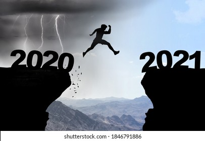 Man jumps over abyss with thunderstorm in background and inscription 2020 and 2021.