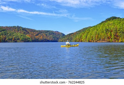 Man Kayaking on a Mountain Lake