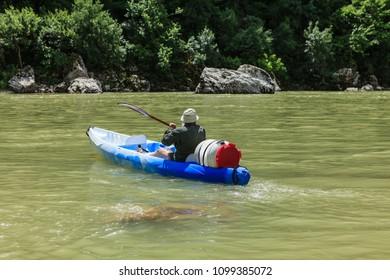 man kayaking on the river
