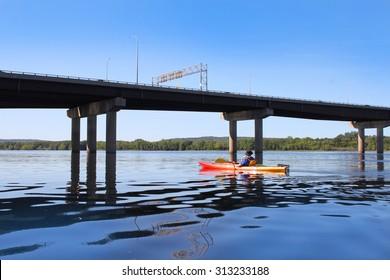 Man kayaking on the Saint John River near  bridge in dowtown Fredericton, New Brunswick
