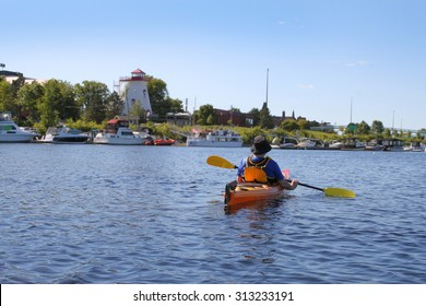 Man kayaking on the Saint John River near downtown  Fredericton, New Brunswick with it's marina and lighthouse on waterfront
