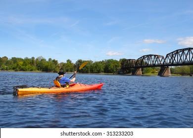 Man kayaking on the Saint John River near a walking bridge in Fredericton, New Brunswick