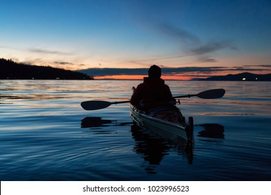 Man Kayaking on a sea kayak during a vibrant sunset. Taken near Jericho Beach, Vancouver, British Columbia, Canada. Concept: Holiday, Adventure, Sport, Fitness, Vacation