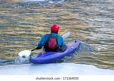 Man kayaking in a purple kayak on an icy river.
