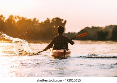 Man kayaking. Rear view of young man splashing water while kayaking on river with sunset in the background