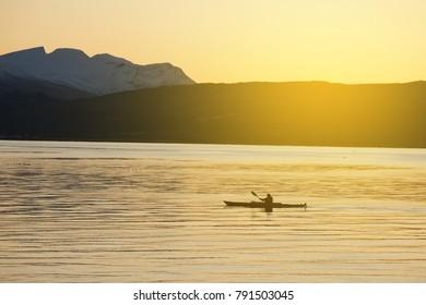 man kayaking at telegrafbukta beach wth snow mountain as background