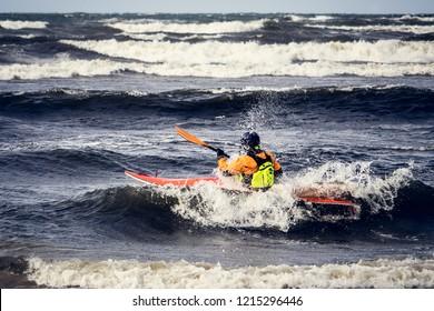 A man kayaking through extreme rough waves.