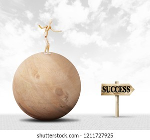 Man keeping balance and standing on the top of a huge wooden ball and moves towards success. Abstract image with a wooden puppet