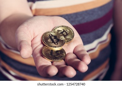 Man is keeping bitcoin cryptocurency coins in his hand