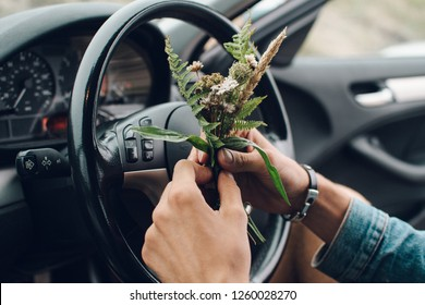 Man keeping a bunch of wild flowers in the car