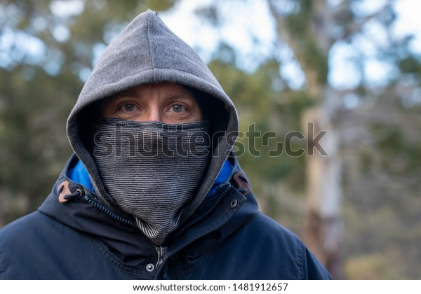 man keeping warm in snow, wearing a beanie hat, with a balaclava over his face to keep warm and staring at the camera.