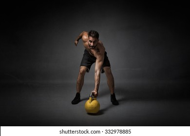 man with kettleball on hand, dark background