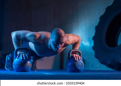 Man with kettlebell weights exercise in the fitness gym. Sports training workout. Functional training. Weightlifting workout. Strength and motivation.