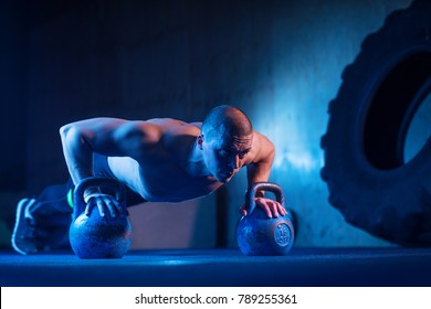 Man with kettlebell weights exercise in the fitness gym. Crossfit training workout. Sports functional training. Weightlifting workout. Sports, cross fit, fitness concept. Strength and motivation.