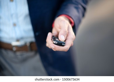 Man with keys. Close up of businessman wearing jacket holding car keys while running late for work