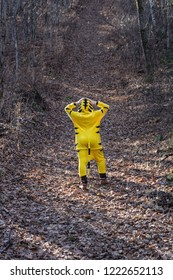 Man in kigurumi tiger suit on forest country road stays backs up to camera lens (back view)