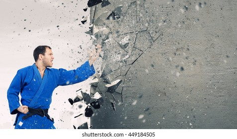 Man in kimono breaking wall . Mixed media