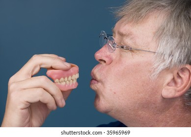 A man kisses his dentures in thanks for allowing him to chew.