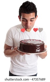 A man kisses one of the heart decorations on a chocolate cake.