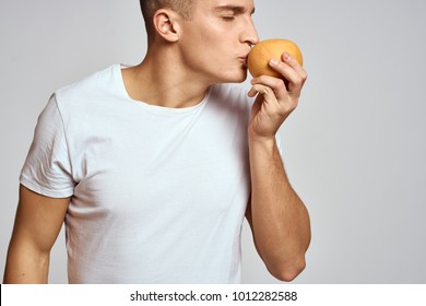 man kisses an orange on a light background