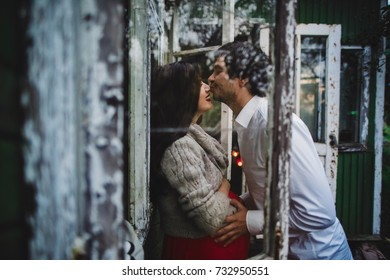 Man kisses pregnant woman in grey sweater standing before an old window