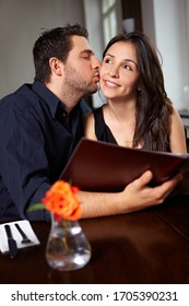 Man kisses woman on cheek in restaurant