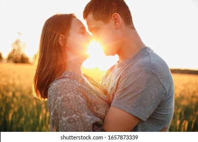 man kisses woman at sunset. kiss with the sun. summer in the field and loving couple. the sun between the girl and the boy