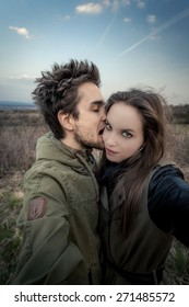Man kissing / biting woman's face. Couple stretching hands to the camera which bought Selfie. In the background withered vegetation with blue sky. Photo in vintage style.