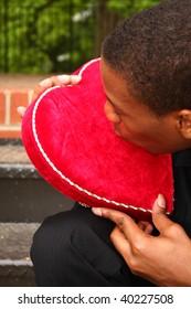 a man kissing a heart shaped box