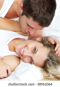 Man kissing his attractive grilfriend in bed
