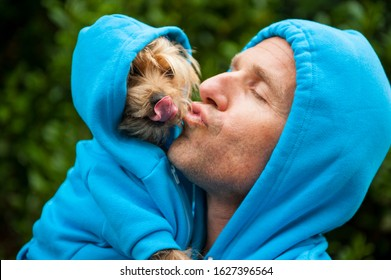 Man kissing his best friend dog in matching blue hoodies outdoors in bright green park background
