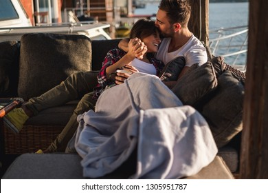 Man kissing his smiling girlfriend in forehead while she is covered with blanket by the river