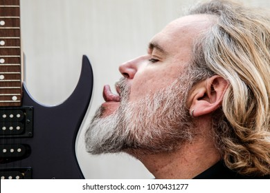 Man kissing and licking his electric guitar
