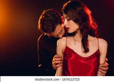 Man kissing shoulder of elegant girlfriend on black background with lighting