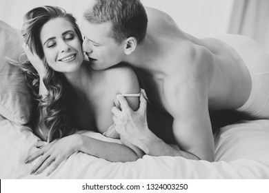 Man kissing smiling woman during romantic sex. Couple embracing in the bedroom