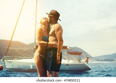 Man kissing a woman in front of yacht. Honeymoon couple enjoying in front of sailing boat