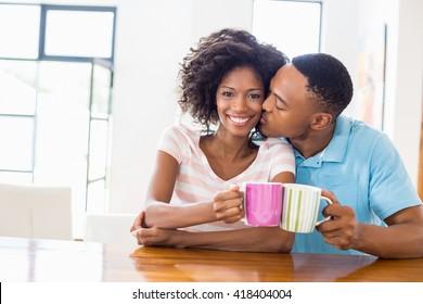 Man kissing woman while toasting coffee mug at home