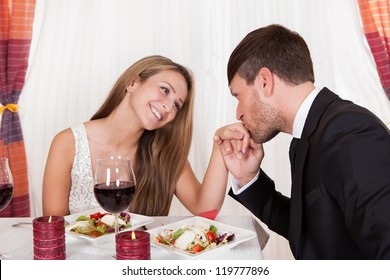 Man kissing a woman's hand at a romantic dinner as she looks at him with an adoring expression and lovely smile
