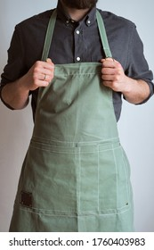 A man in a kitchen apron. Chef work in the cuisine. Cook in uniform, protection apparel. Job in food service. Professional culinary. Green fabric apron, casual stylish clothing. Handsome baker posing