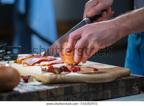 The man in the kitchen cut the onion in half with a knife