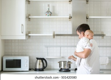 Man in the kitchen holding a child on his shoulder, cooking in the pan. New born, bonding concept photo, family