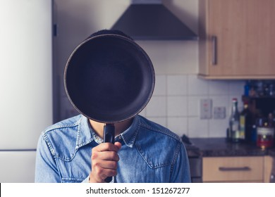 Man in kitchen holding a frying pan in front of his face