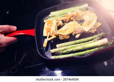 Man in the kitchen preparing chicken with vegetables on a pan