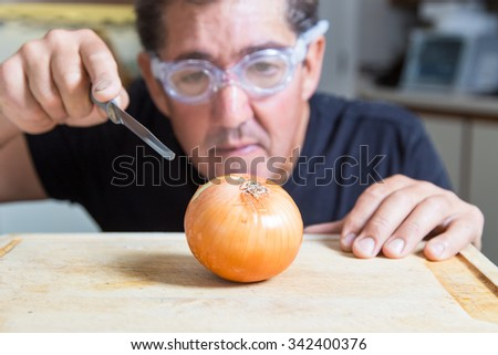 A man in the kitchen tries to cut an onion using goggles to avoid tears, Shallow depth of field with focus on the onion.