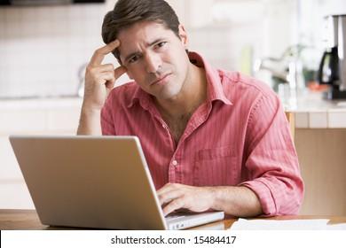 Man in kitchen using laptop frowning